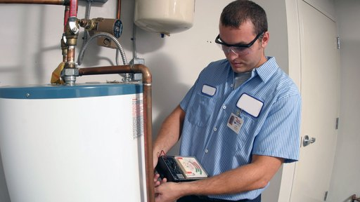 Plumber in the middle of performing a water heater service